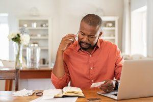 photo of man on phone paying bills